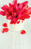 Tulips in vase on wooden surface and  hearts Royalty Free Stock Photography