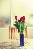 Tulips vermelhos na tabela do terraço Fotografia de Stock Royalty Free