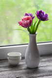 Tulips in a white vase on a light wooden surface Stock Photography