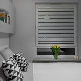 Tulips on windowsill. Yellow tulips on windowsill in white and grey bedroom royalty free stock image