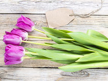 Tulips on wooden background. Tulips with blank tag over wooden background Stock Photo