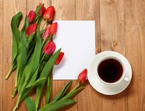 Tulips are on wooden boards, cup of coffee, blank paper sheet for text, greeting concept Stock Photo