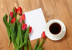 Tulips are on wooden boards, cup of coffee, blank paper sheet for text, greeting concept Royalty Free Stock Photos