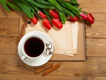 Tulips are on wooden boards, cup of coffee, old sheets of blank paper for text, greeting concept in retro style Stock Photo