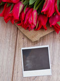 Tulips on wooden table with instant foto Stock Photo