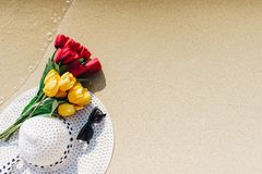 Tulips, yellow and red paste with white sun hat with black sunglasses. On a beach during the holiday weekend Stock Images