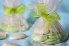 Tulle bags wih wedding dragees. Green and ivory dragees in tulle and organza small bags Royalty Free Stock Images