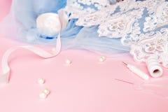 Tulle met kant en kledingstuk op een roze achtergrond Het naaien van een concept van de huwelijkskleding stock foto's