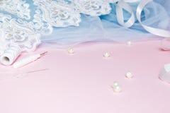 Tulle met kant en kledingstuk op een roze achtergrond Het naaien van een concept van de huwelijkskleding royalty-vrije stock afbeeldingen