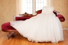 Tulle wedding dress laying on chaise lounge Royalty Free Stock Image