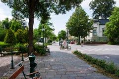 TULLN, AUSTRIA - 31 DE MAYO: La señora monta una bicicleta en una calle verde de la ciudad vieja Imágenes de archivo libres de regalías