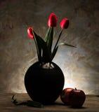 Tulpan i en vas och ett äpple Arkivbilder