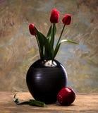 Tulpan i en vas och ett äpple Arkivfoto