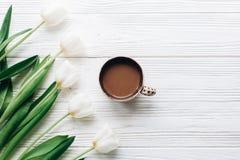 Tulpan och kaffe på vit trälantlig bakgrund stilfull fla Arkivfoto