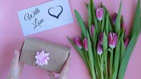 Tulpan på rosa bakgrund Kvinna som sätter hälsningkortet med texten MED FÖRÄLSKELSE och en gåva Direkt ovanför sikt lager videofilmer
