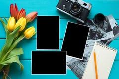 Tulpan, retro kamera för tappning och Notepad med blyertspennan och färdiga foto på en blå träbakgrund arkivbild