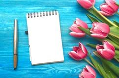 Tulpanblommor och tom anteckningsbokpapperssida på träbakgrund med kopieringsutrymme kvinnadagbegrepp romantisk bakgrund Royaltyfri Foto