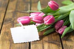 Tulpen auf altem braunem Holztisch mit einem Stickies Lizenzfreie Stockfotografie