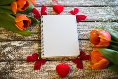 Tulpen auf einem hölzernen alten Hintergrund und einem Notizbuch stockfoto