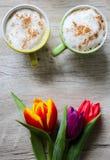 Tulpen auf h?lzernem Hintergrund mit zwei Tasse Kaffees Einladungspostkarte f?r Muttertag oder den Tag der internationalen Frauen lizenzfreies stockbild