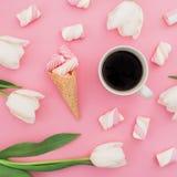 Tulpen blüht mit Becher des Kaffees, der Eibische und des Waffelkegels auf rosa Hintergrund Flache Lage, Draufsicht stockfotos