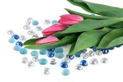 Tulpen die op witte lijst met glasparels leggen stock fotografie