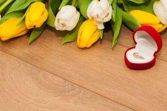Tulpen en zilveren verlovingsring op een houten achtergrond Stock Fotografie