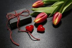 Tulpen, Geschenkbox und rote Herzen Stockfotografie