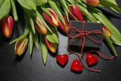 Tulpen, Geschenkbox und rote Herzen auf schwarzem Hintergrund Lizenzfreies Stockbild