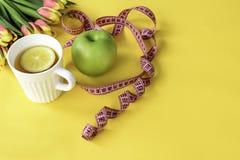 Tulpen, grüner Apfel, Schale Kräutertee mit Zitrone und Maßband auf gelbem Hintergrund Konzept von Frühling Detox Stockfoto