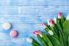 Tulpen met makarons op blauwe houten achtergrond Stock Afbeeldingen