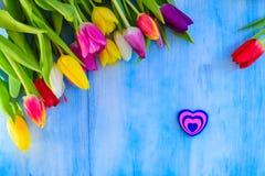 Tulpen mit einem Herzen auf einer blauen Tabelle Lizenzfreie Stockfotos