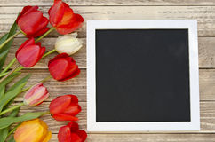 Tulpen mit leerem schwarzem TafelBilderrahmen auf einem hölzernen Hintergrund Romantisches Bild Stockfoto