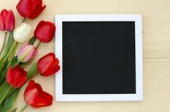 Tulpen mit leerem schwarzem TafelBilderrahmen auf einem hellen hölzernen Hintergrund Romantisches Bild Lizenzfreies Stockfoto
