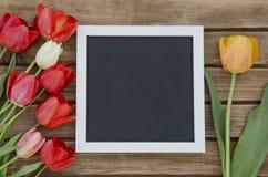 Tulpen mit leerem schwarzem TafelBilderrahmen auf hölzernem Hintergrund Romantisches Bild Lizenzfreie Stockfotos