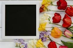 Tulpen mit leerem schwarzem TafelBilderrahmen auf weißem hölzernem Hintergrund Romantisches Bild Lizenzfreies Stockfoto