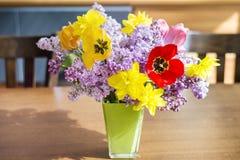 Tulpen-, Narzissen- und Fliederblumen in einem Vase des grünen Glases auf einem Holztisch lizenzfreie stockbilder