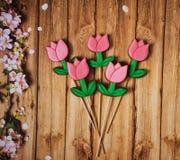 Tulpen op stokken op een houten achtergrond stock afbeeldingen