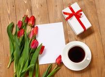 Tulpen sind auf hölzernen Brettern, der Tasse Kaffee, Blatt des leeren Papiers und Geschenk und grüßen Konzept Stockbilder