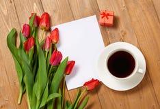 Tulpen sind auf hölzernen Brettern, der Tasse Kaffee, Blatt des leeren Papiers und Geschenk und grüßen Konzept Lizenzfreie Stockfotos