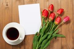 Tulpen sind auf hölzernen Brettern, Tasse Kaffee, Blatt des leeren Papiers mit Platz für Text - Feiertag und Grußkonzept Lizenzfreies Stockbild