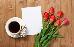 Tulpen sind auf hölzernen Brettern, Tasse Kaffee, Blatt des leeren Papiers mit Platz für Text - Feiertag und Grußkonzept Lizenzfreie Stockbilder