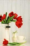 Tulpen und Ei mit Bogen auf Tabelle Lizenzfreies Stockfoto