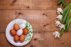 Tulpenbloemen en eieren in de plaat op houten achtergrond Hoogste mening, tekstruimte Stock Foto