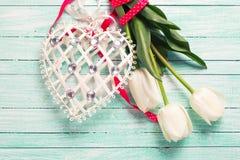 Tulpenblumen und dekoratives Herz auf Türkis hölzernem backgro Stockfoto