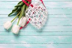 Tulpenblumen und dekoratives Herz auf Türkis hölzernem backgro Lizenzfreie Stockfotografie