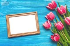 Tulpenblumen und leerer Fotorahmen auf hölzernem Hintergrund mit Kopienraum Frauentageskonzept romantischer Hintergrund Stockfotos
