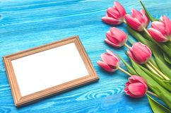 Tulpenblumen und leerer Fotorahmen auf hölzernem Hintergrund mit Kopienraum Frauentageskonzept romantischer Hintergrund Stockbild