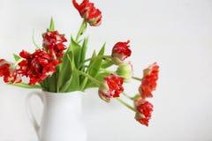 Tulpenblumenstrauß im weißen Vase auf hölzernem rustikalem Stuhl Stockfotografie