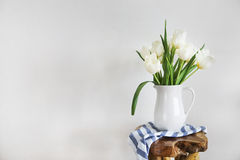 Tulpenblumenstrauß im weißen Vase auf hölzernem rustikalem Stuhl Stockbild